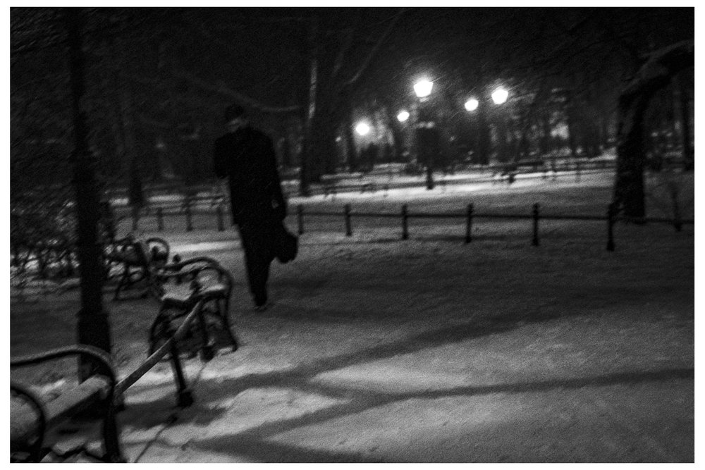 Winter Street Photography; A man in Planty during snowstorm in Kraków.