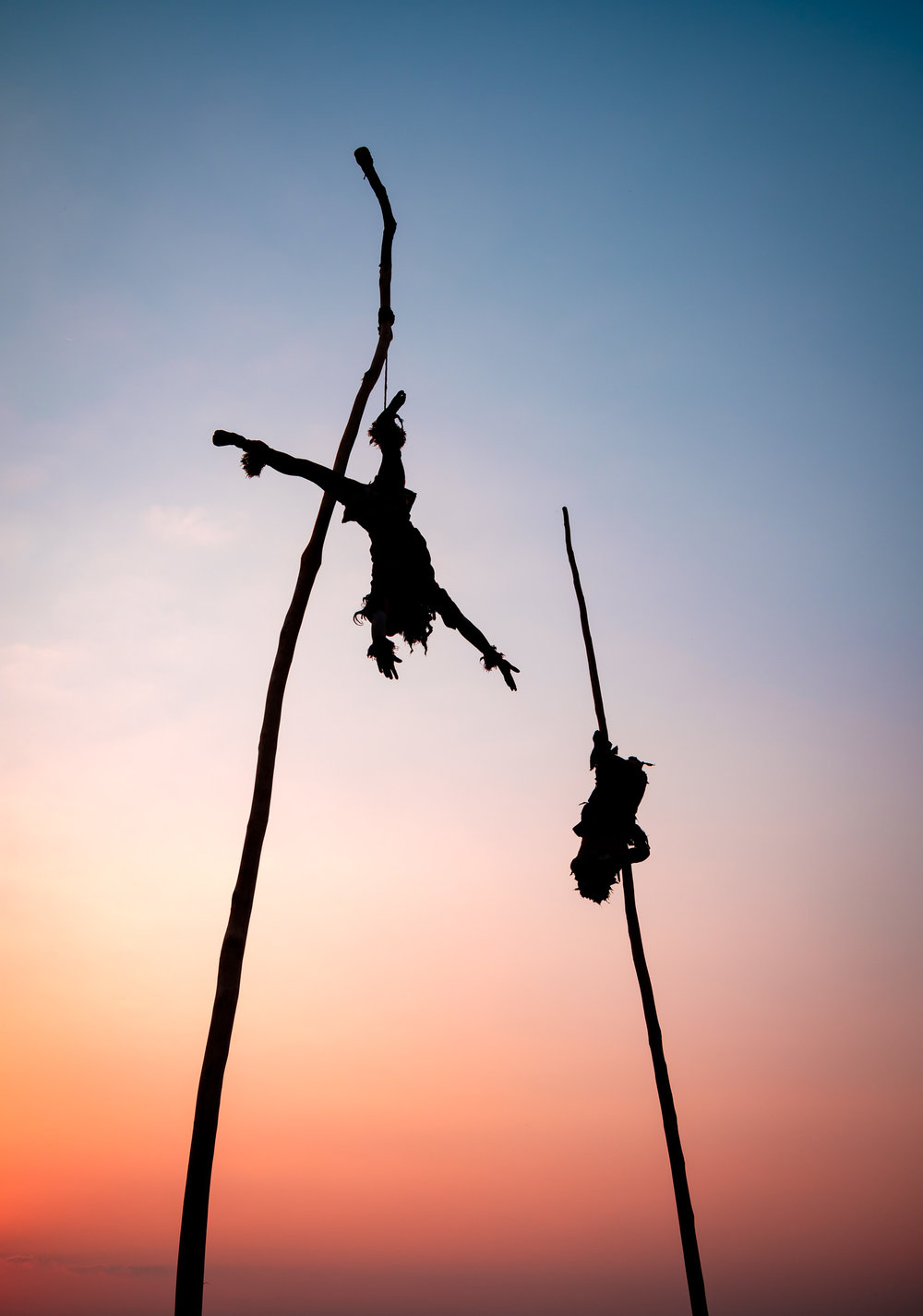 As the sun set you can see the silhouette of the thin rope securing the dancers.