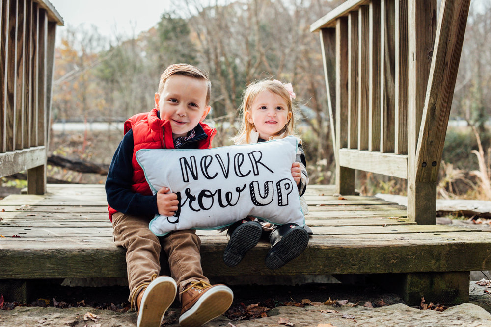 siblings posing with never grow up pillow
