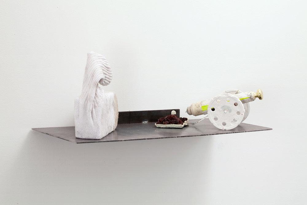 "Luxury Leader War Kit . Grapes, plaster, sock, brick, aluminum, stolen doorknob, steel. 9.5"" x 21"" x 8.5"".2009."
