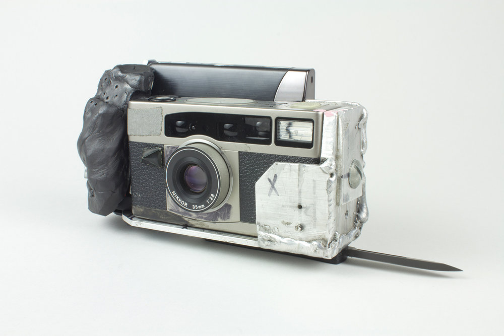 "MACHINE_GUN_VIEWER . Porcelain, aluminum, 35mm bloggy cam, switchblade. 11"" x 1.75"". 2014."