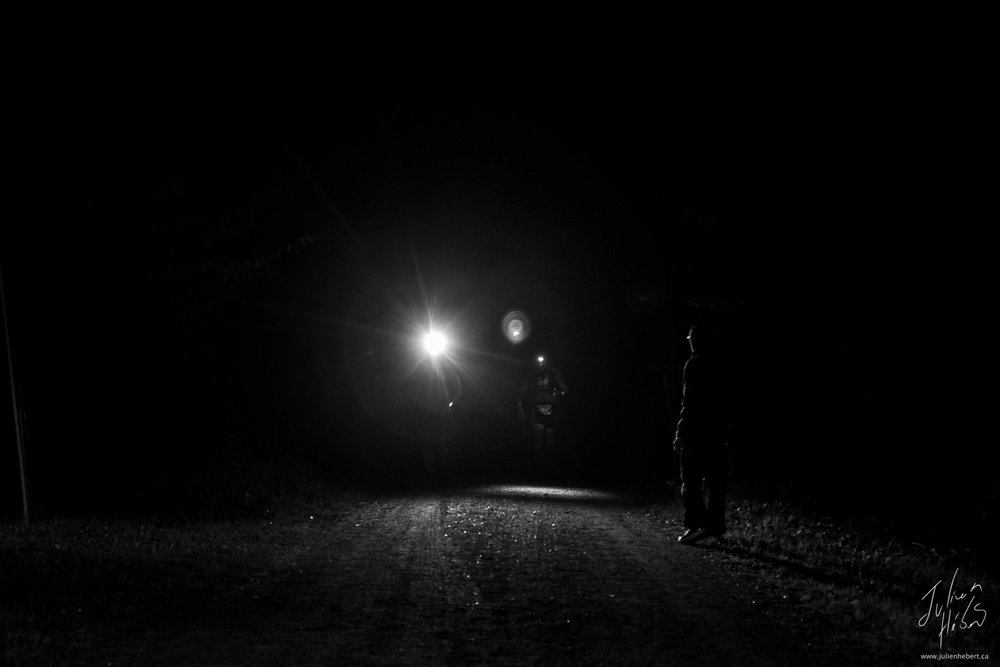 Le meneur et son pacer qui sortent de l'obscurité à leur arrivée au P7 dans la nuit de samedi à dimanche.