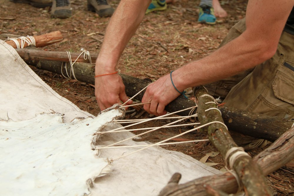 Pictured: Stringing up a hide in a round wood frame made of bush poles cut on site.