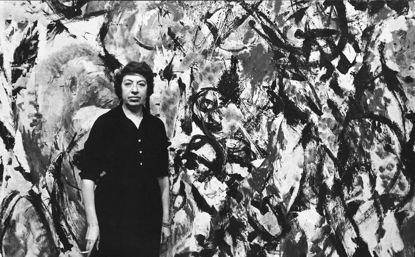 Portrait of American artist Lee Krasner in front of one of her paintings, New York, 1950s