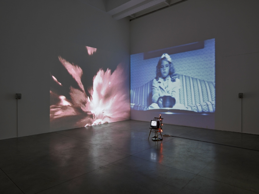 Susan Hiller,  Wild Talents , 1997 Video installation: two channel video projection, with sound, one black-and-white video, monitor, chair, and votive lights. Dimensions variable. © Susan Hiller. Courtesy Lisson Gallery