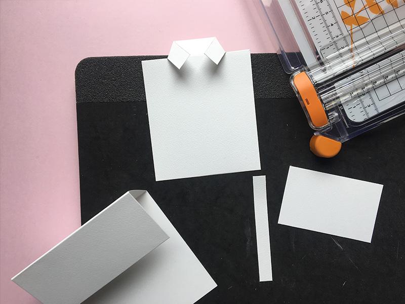 Step 5:  af resterne fra kortbase 2 klippes to firkanter: En til skjorte: 1 cm x 9 cm og en til bund: 8 cm x 5 cm (se skabelon og foto). Du har nu 4 hvide dele fra dine kortbaser.