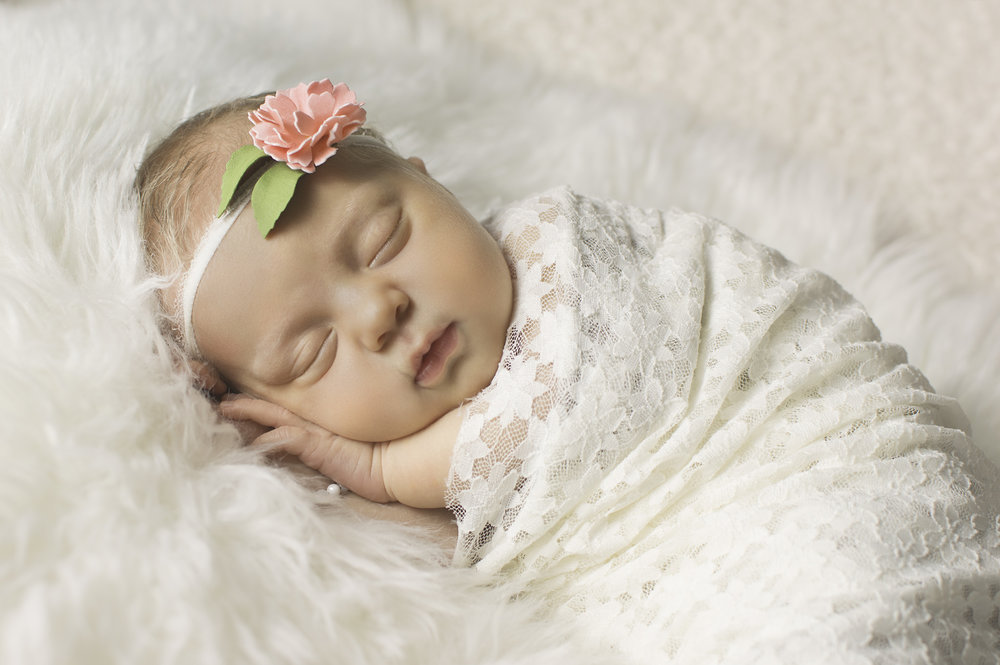 newborn wrapped in white lace with flower headband