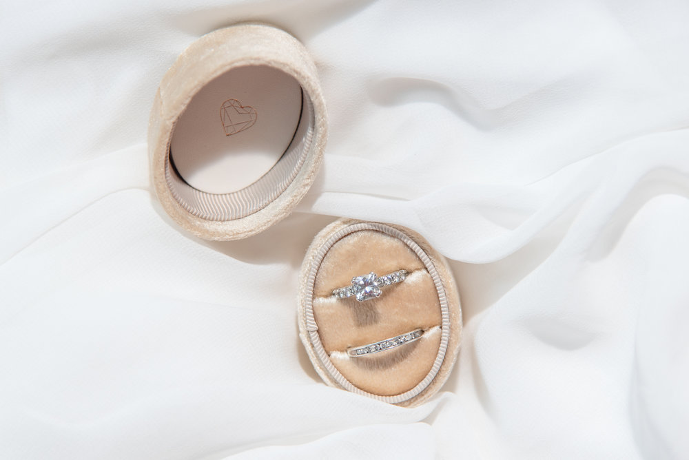 engagement ring and wedding band in champagne ring box
