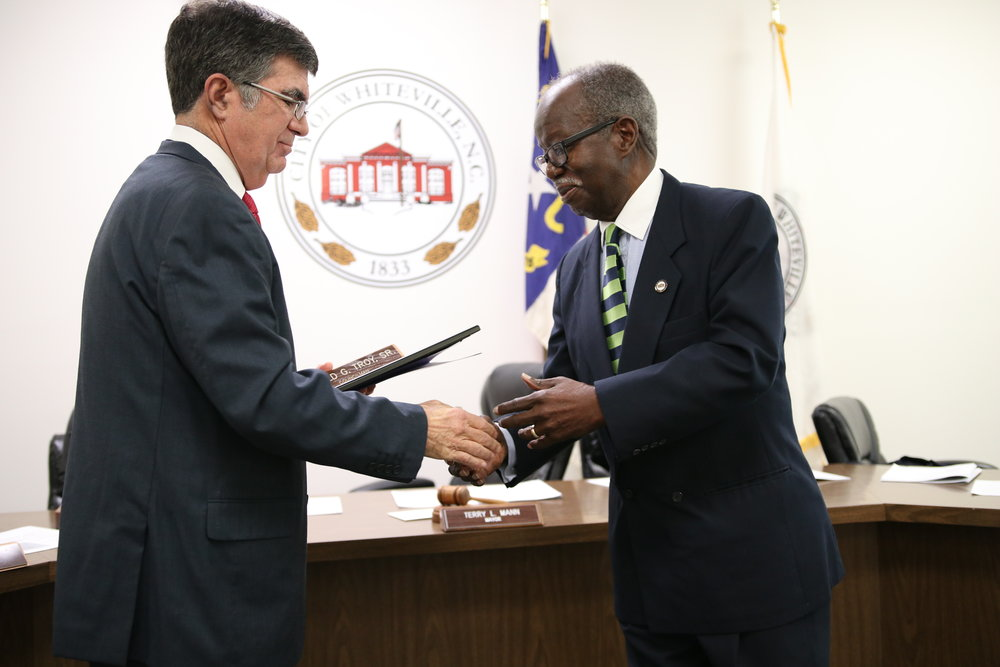 Harold Troy accepts his certificate of service and name plate from Mayor Terry Mann.