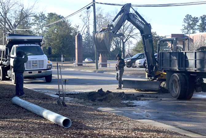 Garrett Bullock, Jaquan Jones and Ethan Dudney work at the site of the water line break on Lee Street.