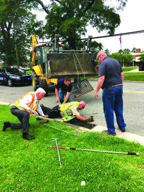 Animal Control Officer Darryl Hooker goes into the storm drain to save a calico kitten Tuesday. Fire Marshall Hal Lowder monitors the rescue with Travis Faulk and Mark Coleman of the city's Public Works Department.