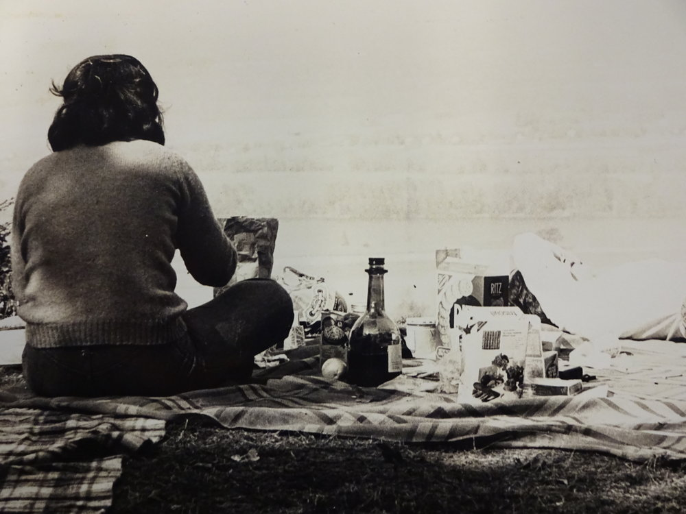 Photo courtesy of Archives and Special Collections During a 1970s Mountain Day, a Mount Holyoke student has a picnic on the grass with Ritz crackers and spirits.