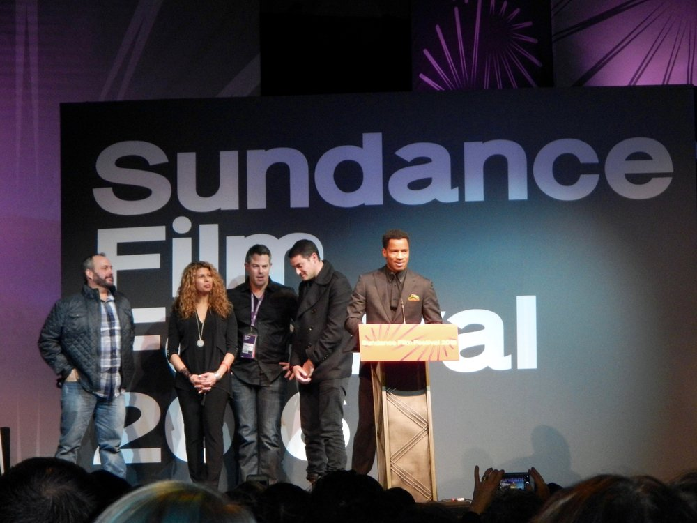"Photos Courtesy of Flickr Nate Parker stands at the podium during the premiere of ""The Birth of a Nation"" at the 2016 Sundance Film Festival."