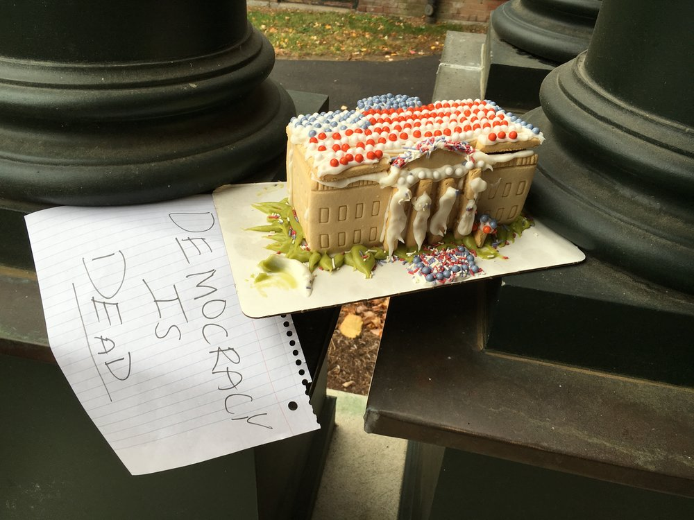 Photo by Hannah Roach '17 A cake in the shape of the White House rests on a sign declaring the death of democracy on Nov. 9, 2016.