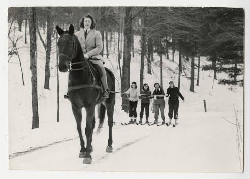 jane senter '45 on horseback pulling four other students up mountain on skiis 1945.jpg