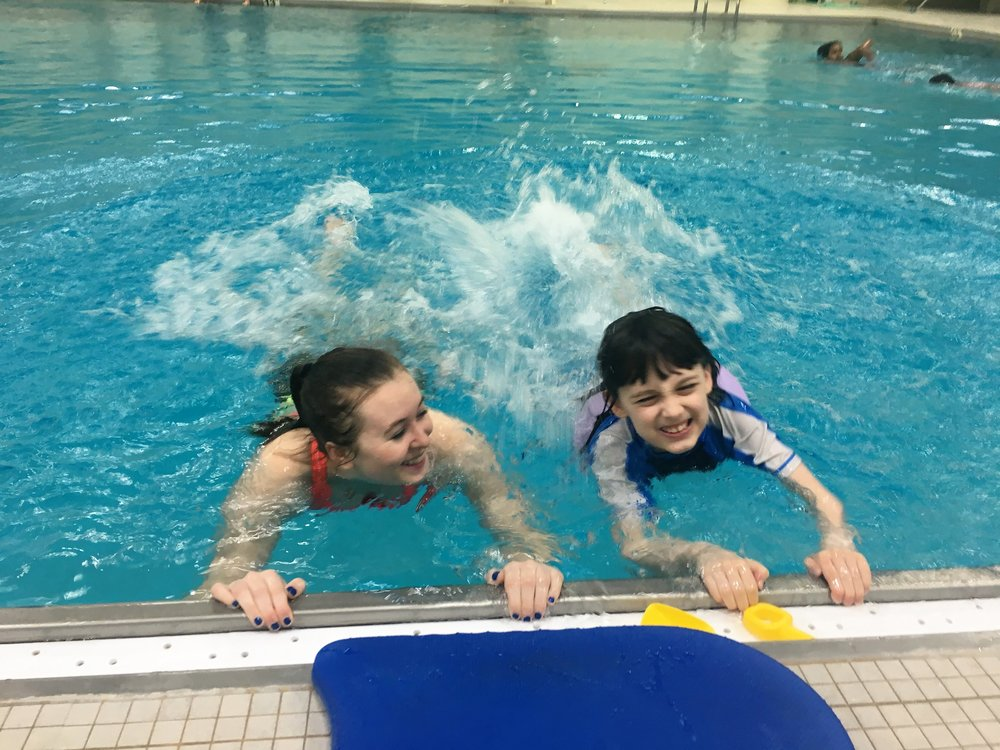 Photo by Ruth Wondimu '19 Volunteer Isabell Linde '19 provides swimming lessons to a local child as a part of Project Splash at MHC.