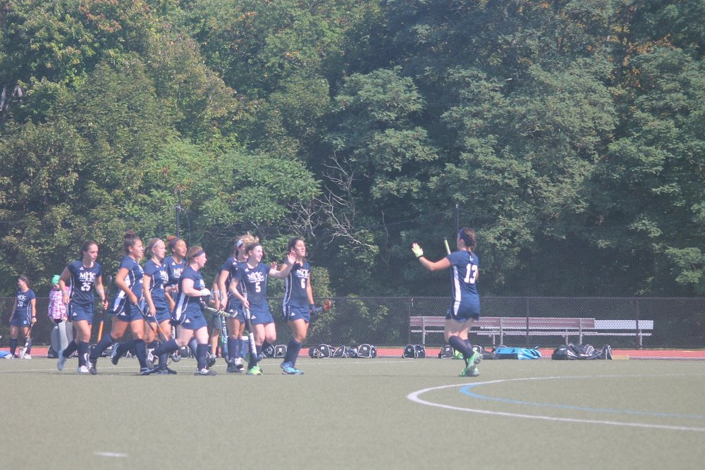 Photo by Emily Pollack '20  Mirjam Keochakian '19 runs to high-five her teammates during their game against Clark University on Saturday afternoon. With three goals from Keochakian, they defeated the Cougers 6-1, securing MHC's 13th victory.