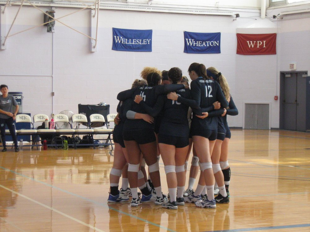 Photo by Emma Himmelberger '20  Mount Holyoke Volleyball huddles together during a time out, arms crossed as their coach goes over a game plan. Pictured in the center are teammates Jamesa Aleen '19, Sasha Simine '20 and Melissa Stewart '19,
