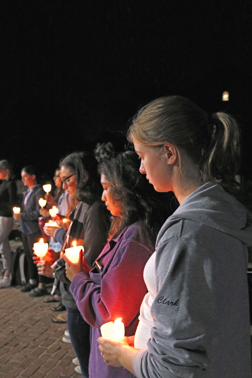 Emily Clark '18 and other attendees held candles Friday during the vigil for victims of natural disaster in Mexico and Puerto Rico