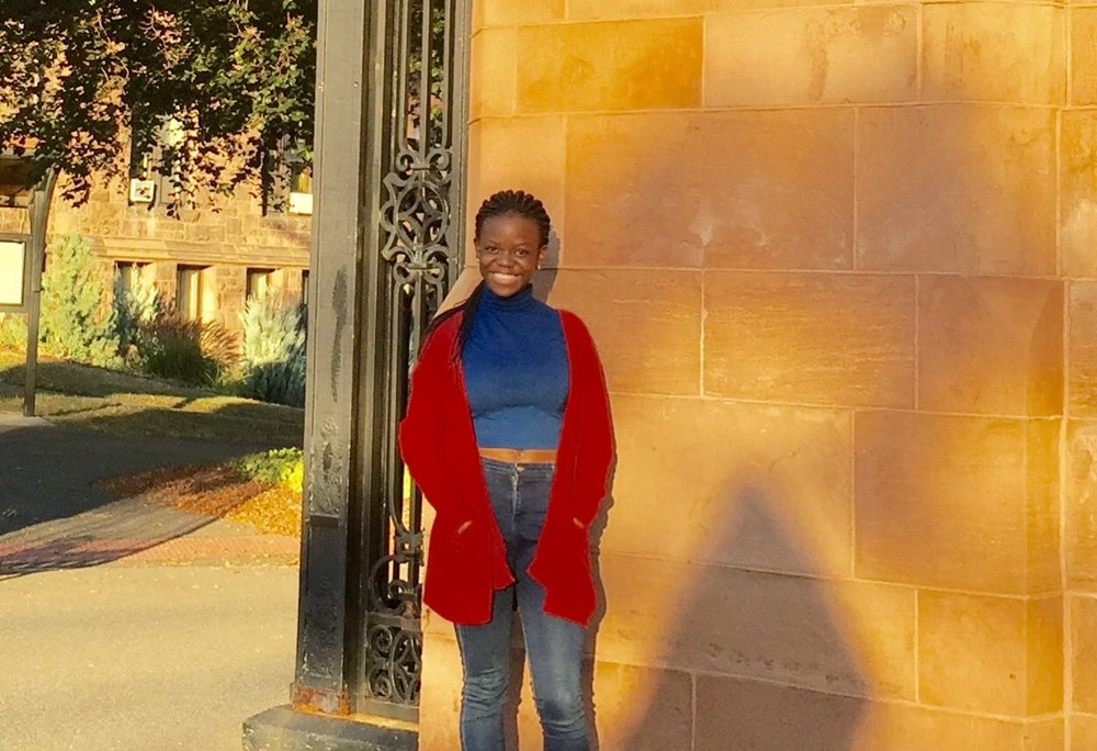 Angela Nayiga '20, a spring semester admit from Uganda standing next to the front gates of Mount Holyoke College