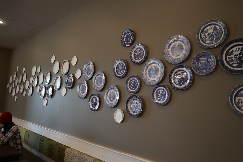 Photo by Yingke Yang '20  Blue and white Mount Holyoke china, contributed by President Stephens and the Alumnae Association, now decorates the walls of the Dining Commons.