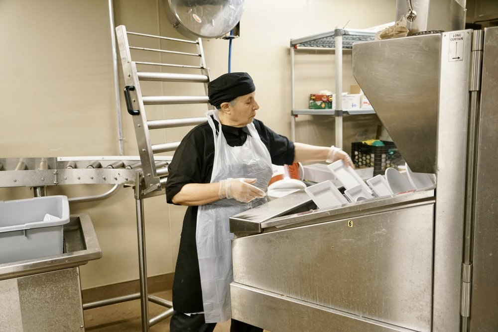 Photo by Yuer Zhang '21  Soffan Russasosfsan, a Mount Holyoke Dining Services employee, loads dishes on to a conveyer belt.