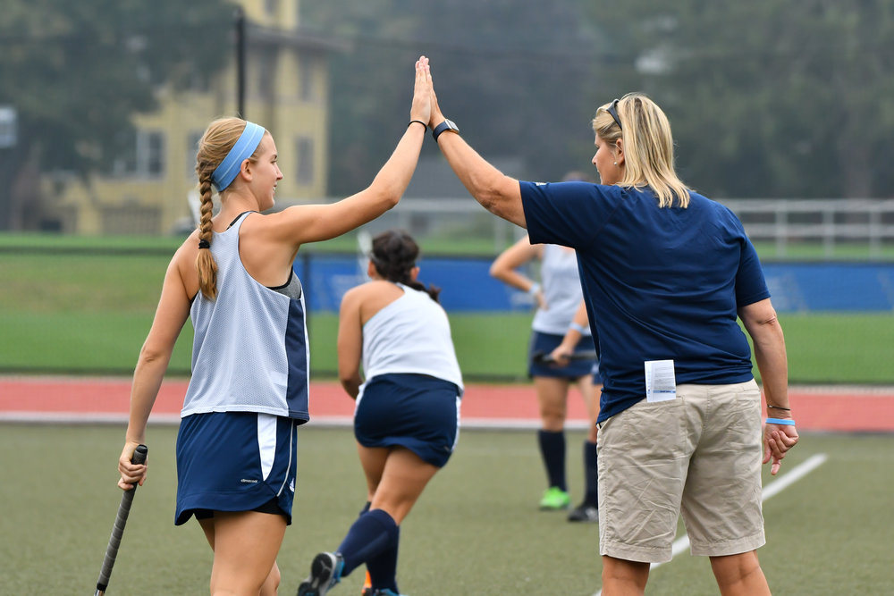 Photos courtesy of RJB Photography  Field hockey Head Coach Andy Whitcomb and midfielder Kristina Ramsden '18 high-five during game warmups.