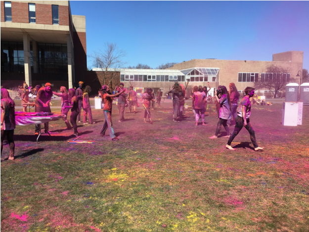 Photo by Casey Roepke '21  Students dance and throw colored powdered on the lawn.