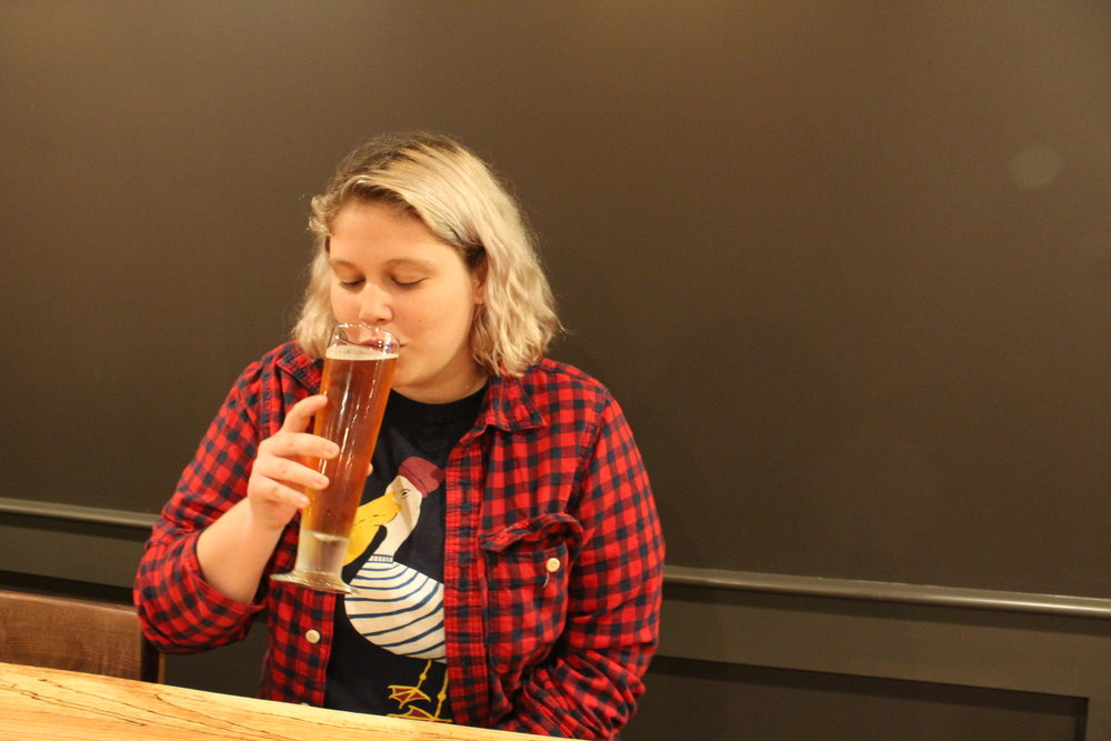 Photo courtesy of Izzy Burgess '19  Lily D'Anieri enjoys a Sam Adams beer in the new Cochary Pub & Kitchen on the lowest floor of Blanchard Hall.
