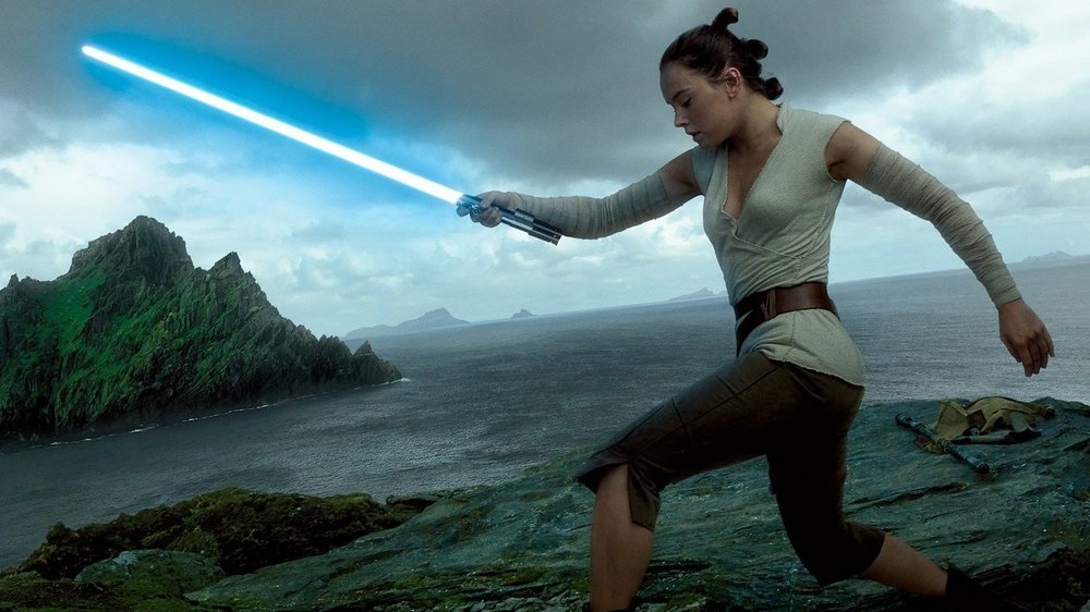 Rey (Daisy Ridley) wields a lightsaber in her Jedi training on the planet of Ahch-To.