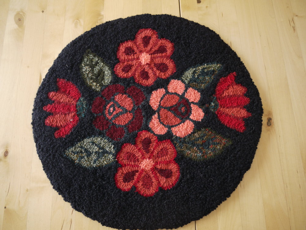 Floral Chair mat. Moose River Rug Hooking design.  Combination of traditional hooking with wool fabric strips for the flowers and leaves. Punch needle technique with wool yarn for the black background.