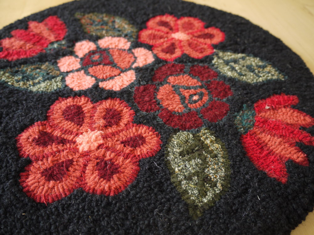 Black & Coral chair mat.  Here you can see the traditionally hooked flowers and leaves in contrast with the punch needled background.