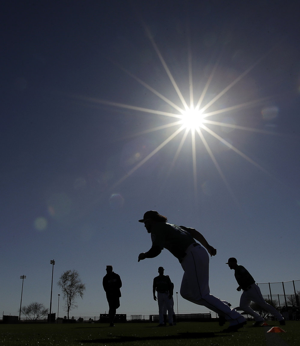 Players for the Seattle Mariners run drills during a baseball practice in their spring training. The implementation of the new rules will ultimately speed up the game of baseball, recapturing the attention of fans.(Charlie Reidel/AP Photo)