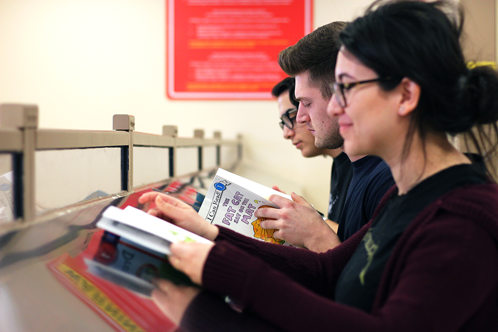 Geneseo's Features and Opinion Writing class is working with inmates from the Livingston County Jail to record them reading children's books to send to their children. Pictured above are junior Rebecca Buchman, senior Colby Burke and junior Johnathan Saponara, working on the project. (Ash Dean/Photo Editor)