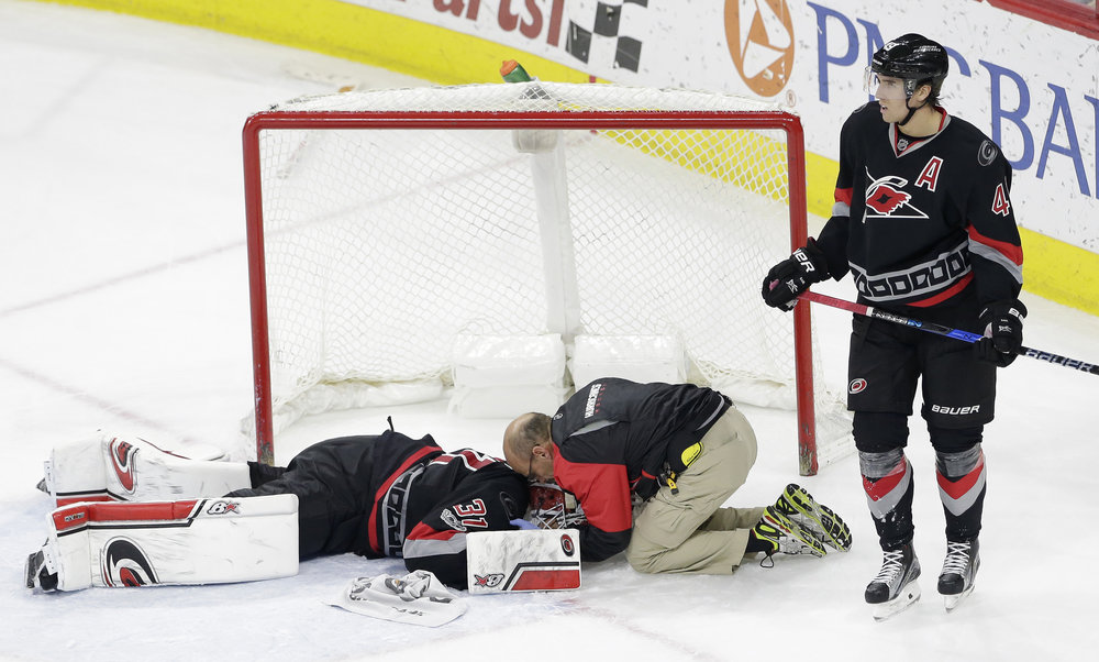 Carolina Hurricanes goalie Eddie Lack is treated on the ice for an injury during a game against the Detroit Red Wings in Raleigh, North Carolina on Monday March 27. A trainer or sports doctor must be readily available at all times for their athletes, especially during a competitive game. (Gerry Broome/AP Photo)
