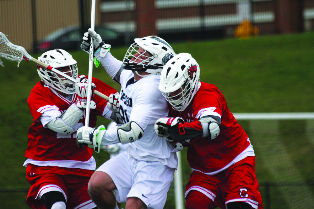 Sophomore defender Jack Crowley fights to maintain possession against the SUNY Cortland forwards during their game on Wednesday April 12. The men fell to Cortland 12-8 on their home turf, but hope to be successful during their next game against SUNY Potsdam. (Ash Dean/Photo Editor)