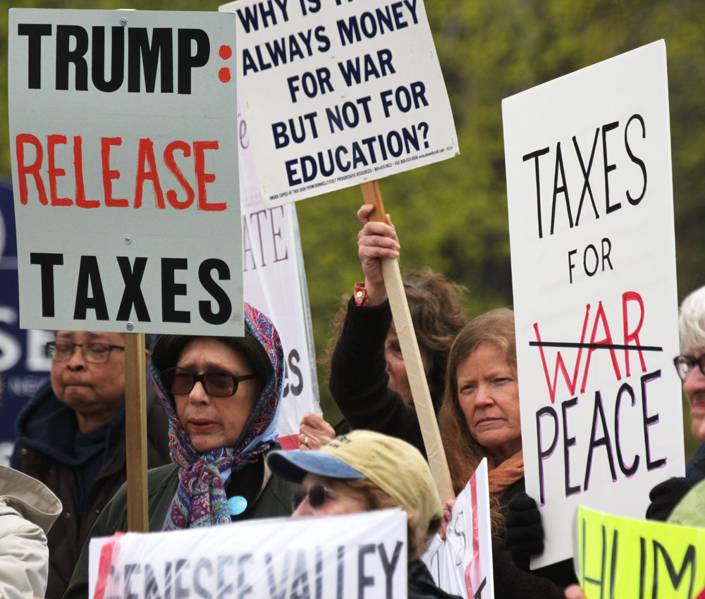 Members from the Geneseo community protested outside of Congressman Chris Collins' office on Wednesday April 19 against President Trump's tax revenue plan. Attendees hope that such action will aid in convicing Collins to listen to his constituents. (Ash Dean/Photo Editor)
