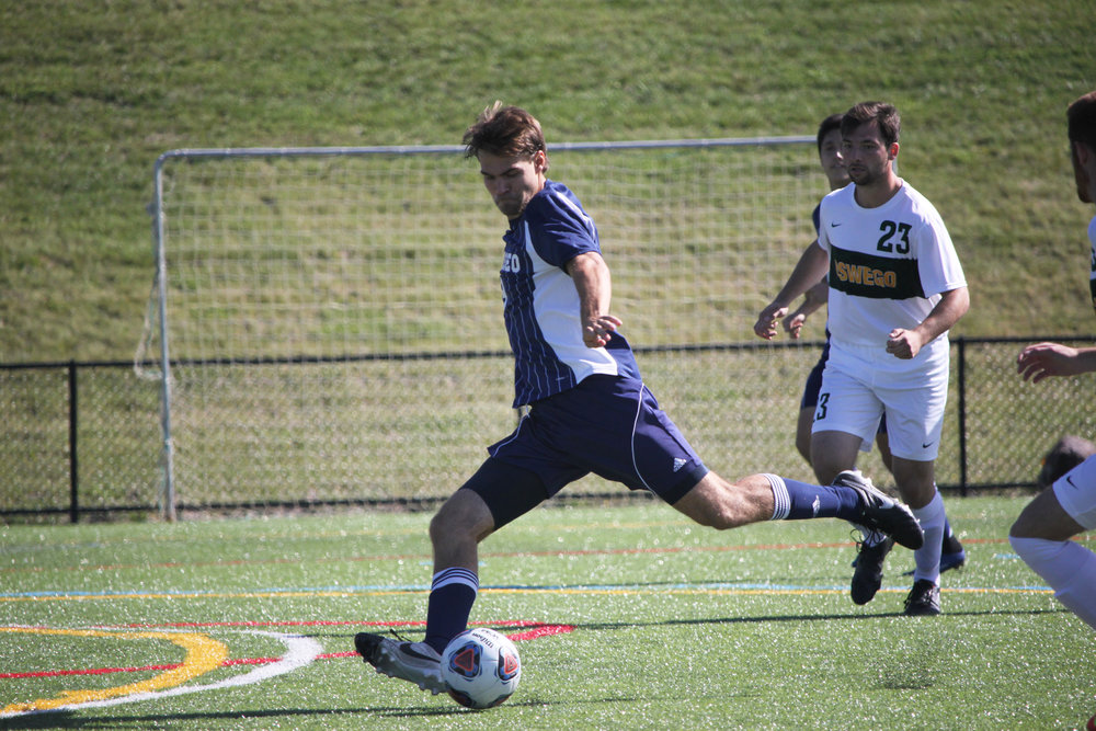 Senior midfielder Matt D'Amico looks to send the ball up the field during a game against SUNY Oswego. Despite having a younger roster, the men finished off strong with a record of 9-7-2. (Ash Dean/Photo Editor)
