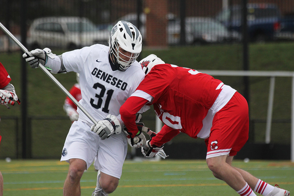 Sophomore defender Jack Crowley takes a hit from a SUNY Cortland forward during their game on Wednesday April 12. The men look to fight for a playoff spot against SUNY Oneonta on Saturday April 29. (Ash Dean/Photo Editor)