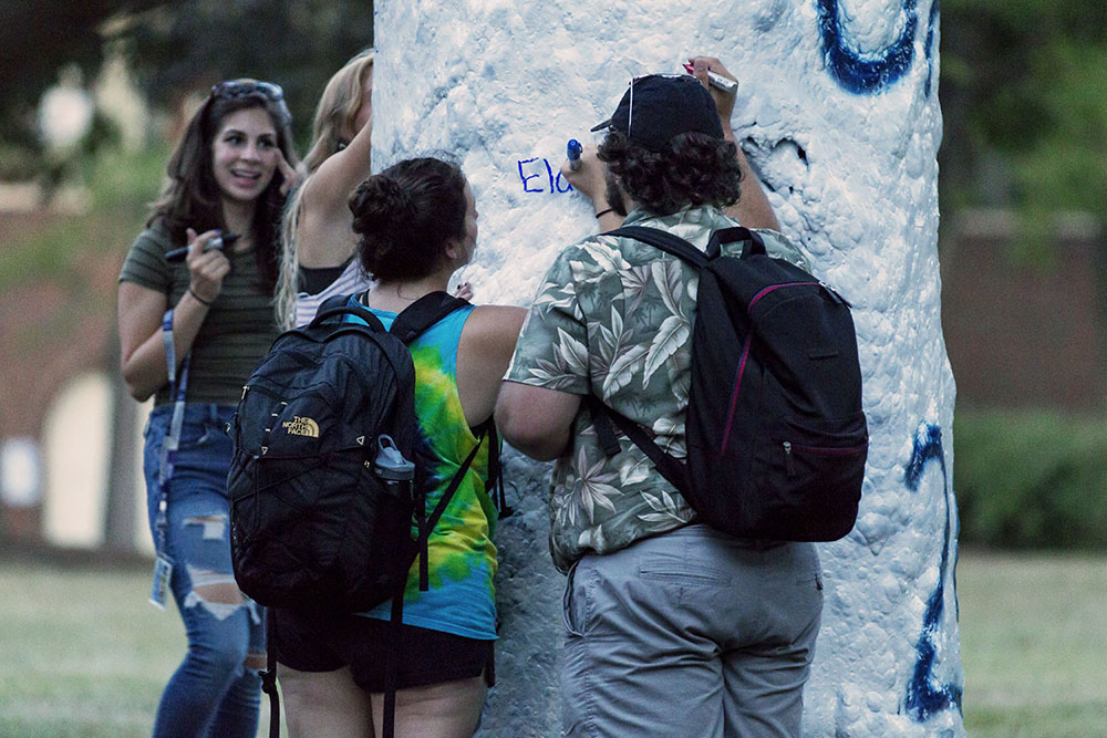 Students paint the Greek Tree,  showing their pride by painting their letters or signing members' names. Greek organizations offer great benefits to students despite the negative stigma often surrounding them. (Annalee Bainnson/Photo Editor)