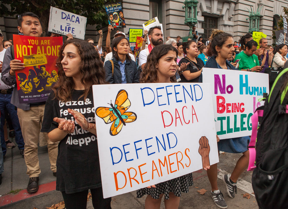 Young female protestors hold posters at a DACA rally in San Francisco on Sept.  5. Geneseo, as an institution, must take increased actions when it comes to supporting students influenced by the DACA program. (Pax Ahimsa Gethen/Creative Commons)