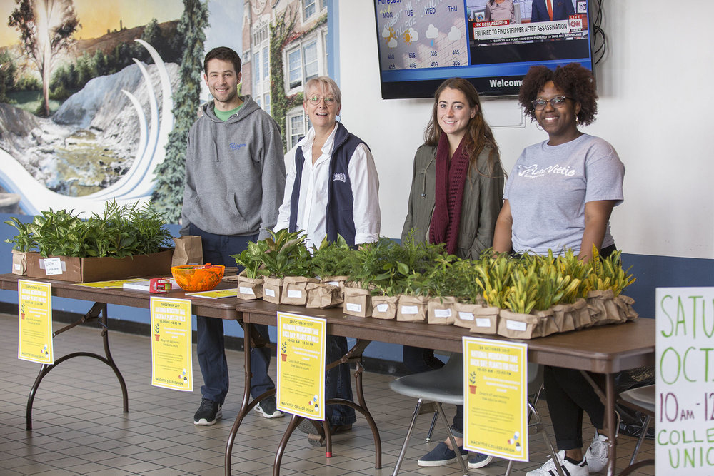 "Pathways peer advocate and Alcohol and Other Drugs advocate senior Harrison Moses, AOD program coordinator Sarah Covell and Department of Student Life interns for sustainability seniors Julia Depillo and Eunisha Tucker helped at the ""National Medication Takeback Day: Plants for Pills"" event on Saturday Oct. 28 (pictured above left to right). Attendees had the opportunity to get rid of unwanted perscription medication safely and receive a plant in return. (Annalee Bainnson/Photo Editor)"