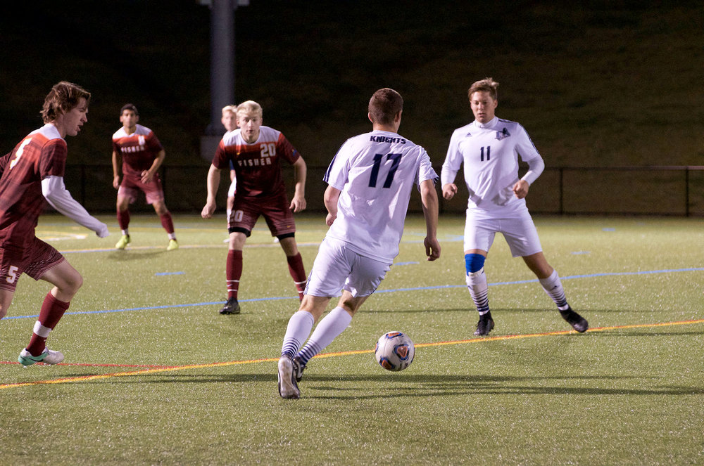 Junior defender Greg Baumstein sets up a pass to senior midfielder Alex Clar during a game against St. John Fisher College on Oct. 25. Despite their hard work, the men fell short in the SUNYAC Tournament with a 0-3 loss to SUNY Oneonta, which eliminated the Knights.