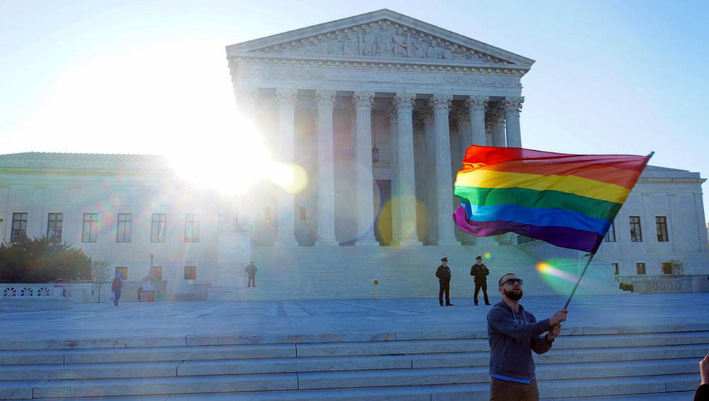 An individual waves the gay pride flag outside of the United States Supreme Court in April 2015. The vote in the United Nations to allow the death penalty for same-gender relationships is disappointing and seems regressive considering the progress made by the LGBTQ+ community recently. (Ted Eytan/creative commons)