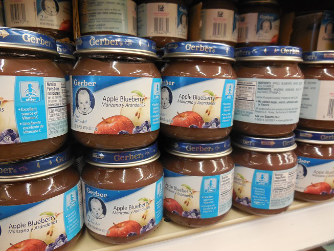 """Gerber Apple Blueberry Jarred Baby Food (pictured above) on a store shelf. The popular baby food brand is inspiring children and parents to accept all individuals. The company has announced their first """"Spokesbaby"""" with a Down syndrome. (Courtesy of Creative Commons)"""