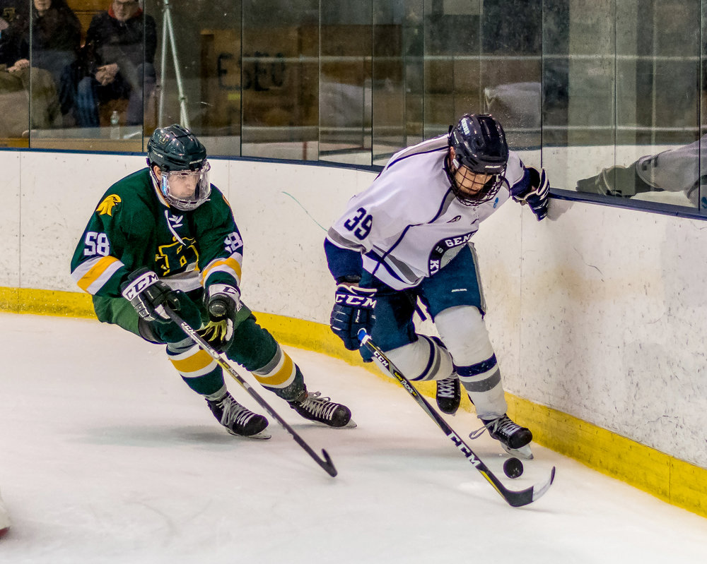 Junior forward Arthur Gordon shields the puck along the boards from a SUNY Brockport defender on Saturday Feb. 17. The Ice Knights defeated Brockport 1-0, and intend to continue this success throughout their duration in the SUNYAC Tournament. (Jon Pastore/staff photographer)