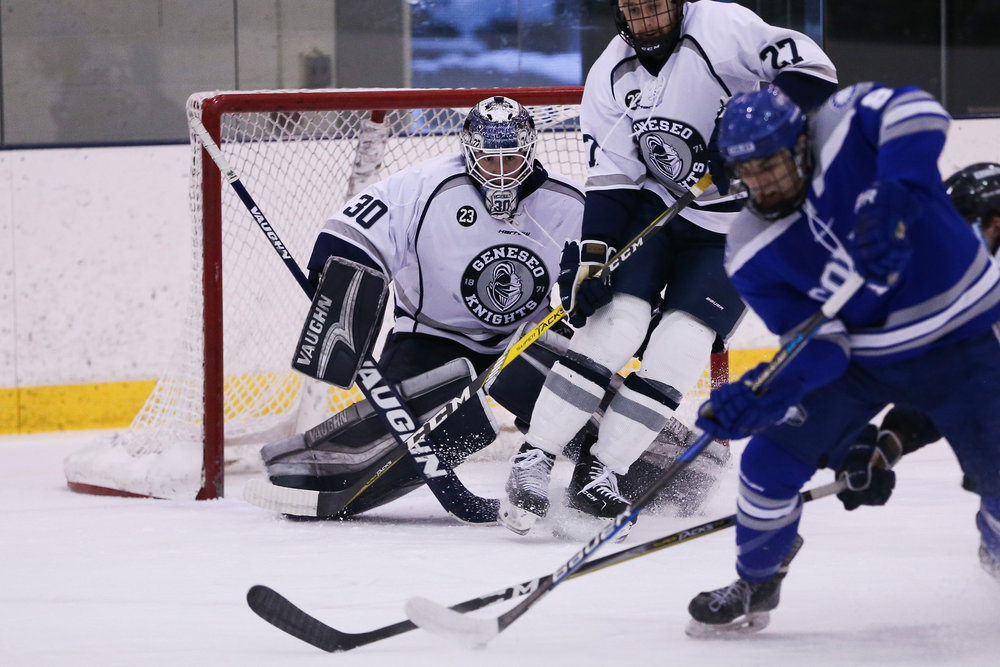 Senior defender Pat Condon (pictured left) sets up for a slap shot against Colby College. Junior goaltender Devin McDonald prepares to stop a shot from a Colby forward (pictured right). The Ice Knights hosted Colby in the NCAA Quarter finals on Saturday March 17, but suffered a 2-1 loss within the last few seconds of play. The men look to return to the ice next season where they will defend their SUNYAC Title. (Keith Walters/director of multimedia)