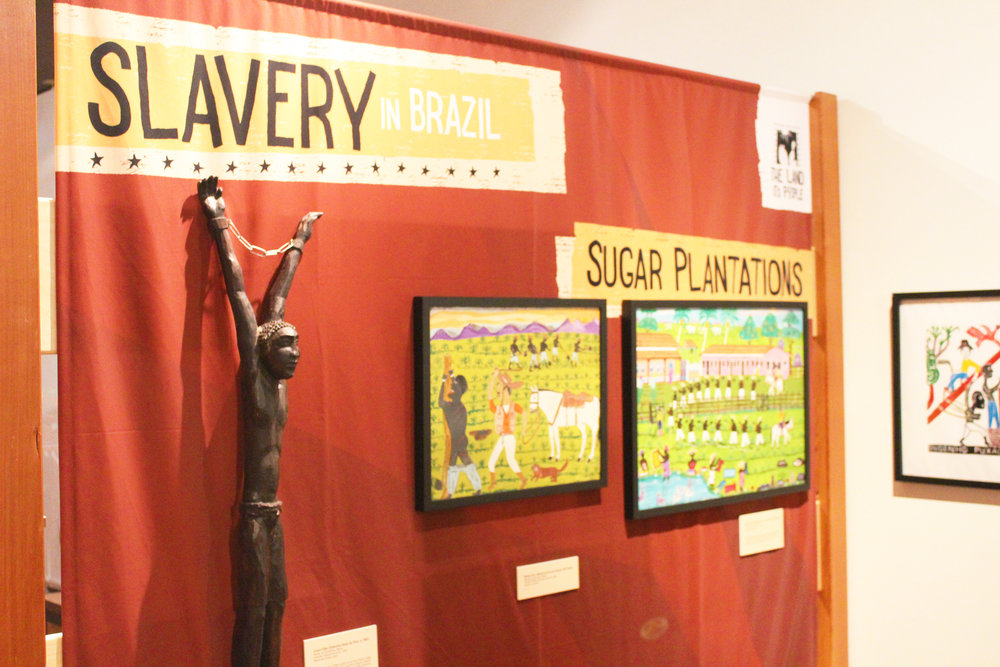 "The ""Bandits & Heroes, Poets & Saints"" exhibit showcases several sides of Brazil, including slavery, a theme reflected in the art above. The slavery section of the exhibit is categorized under ""The Land and its People,"" which also includes art featuring cowboys, immigrants and other individuals important to the history of Brazil (Whitley Brincka/Staff Photographer)."