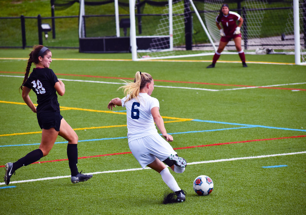 First-year forward Nicole Bell attempts to send a ball into the box as a defender closes in on the Knights' Saturday Sept. 22 matchup against SUNY Plattsburgh. The game ended in a 1-0 victory (Josie Kwan/assoc. photo editor).