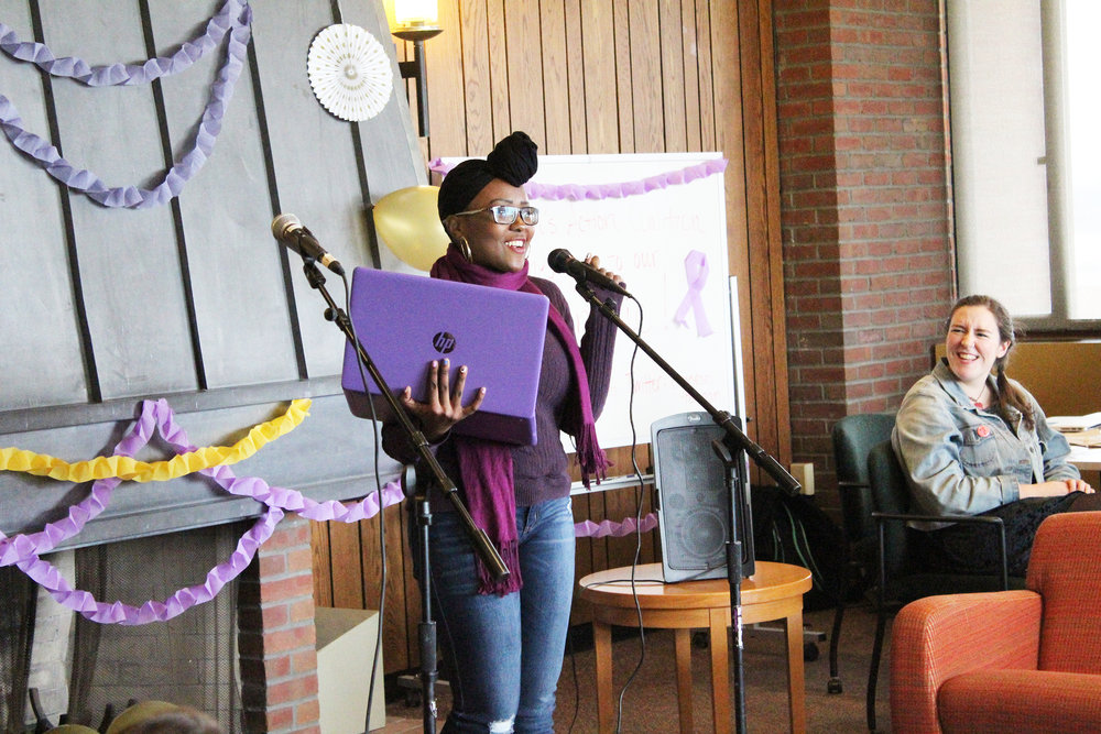 Biology major freshman Vimbayi Mandizha (pictured left) read poetry as audience members like Women's Action Coalition vice president Jennifer Galvao (pictured right) watched at the open mic event on Sunday Oct. 21. The event was organized to raise money for victims of domestic violence (Catherine White/editor-in-chief).